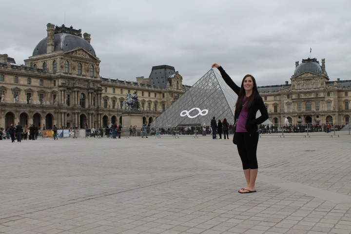 "As you can tell from the pic above, it literally took 50+ attempts for my mom to get a picture of me truly holding the top of the pyramid.  Because of her bad knees, she couldn't squat and instead had to do a deep runner's lunge to get the right angle for the picture.  I was DYING laughing at her because she looked like she was trying to do yoga at the Louvre.  It is still one of my favorite memories from the trip because she looked so silly & we were trying for probably 15 minutes to get this dang picture!  For the rest of the trip, anytime she wanted me to smile for a picture, she just had to bring up ""yoga at the Louvre"" and I would start cracking up :)"