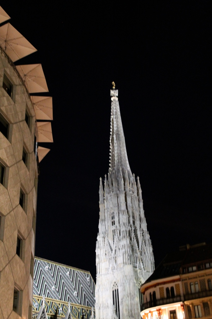 Juxtaposition of the modern building, on the left, with the old cathedral spire, at night!
