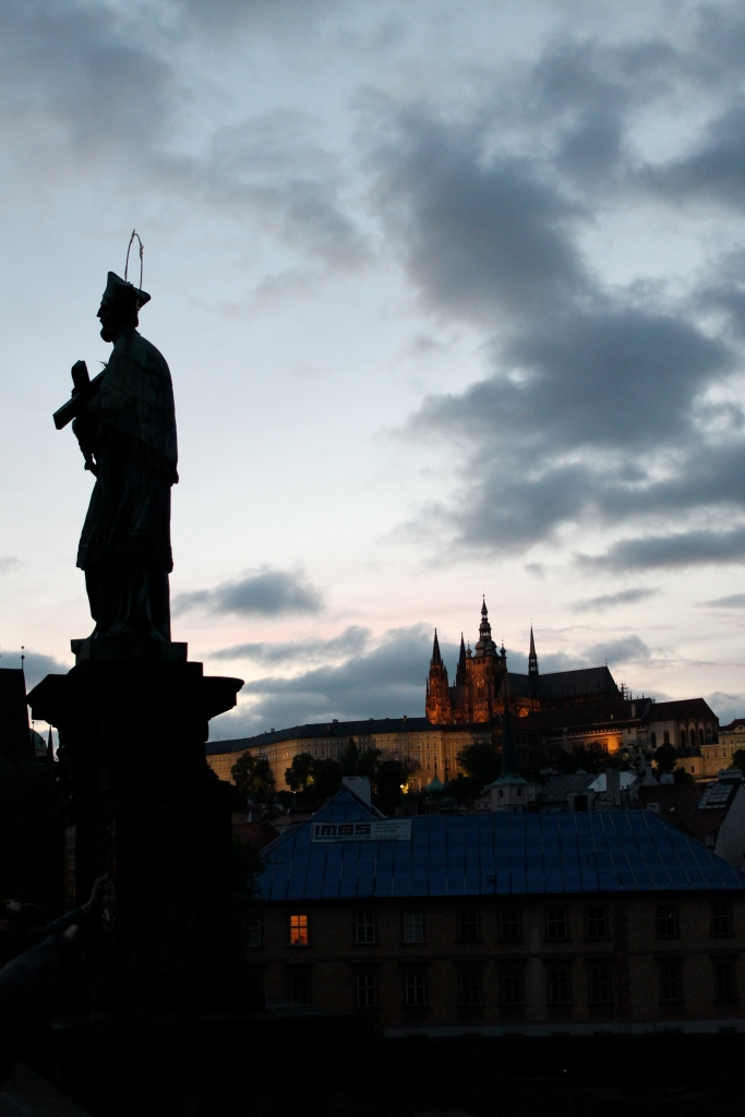 Prague Castle illuminated, with one the most famous statue on St. Charles Bridge up front